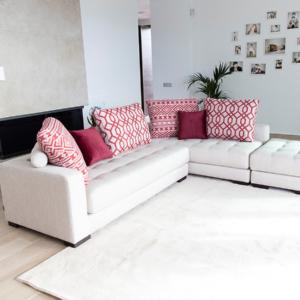 γωνιακός καναπές λευκός με κόκκινα μαξιλάρια